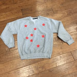 Image of a grey sweatshirt with bright red stars by John Eshaya.